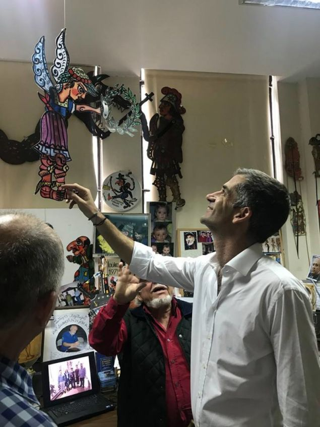 Ο υποψήφιος δήμαρχος Αθηναίων ευδιάθετος περιεργάζεται φιγούρα καραγκιόζη