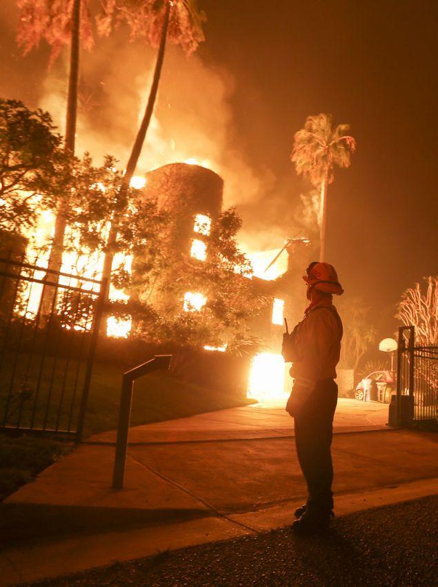 Πυροσβέστης παρακολουθεί, ανήμπορος πλέον να αντιδράσει, την πύρινη λαίλαπα να κατατρώει μια κατοικία στο Μαλιμπού (Φωτογραφία: ΑΡ)