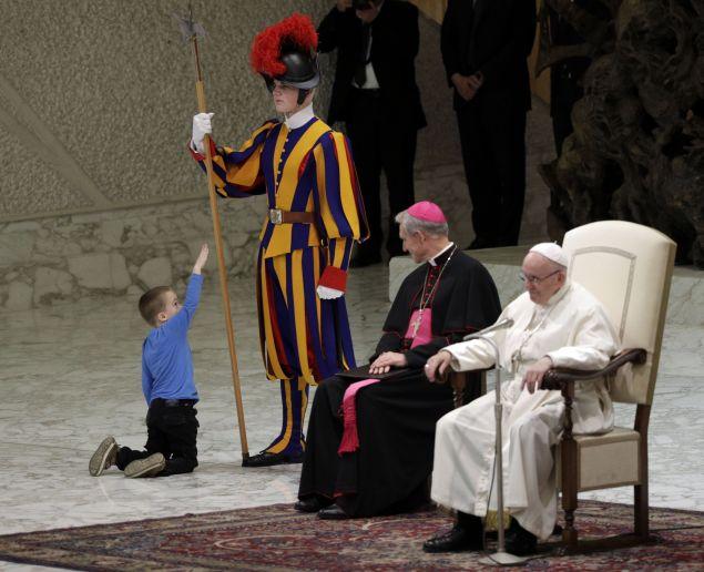 Το παιδί τράβηξε το χέρι ενός Ελβετού φρουρού και  έπαιξε ανέμελα πίσω από την παπική πολυθρόνα./Φωτογραφία: AP