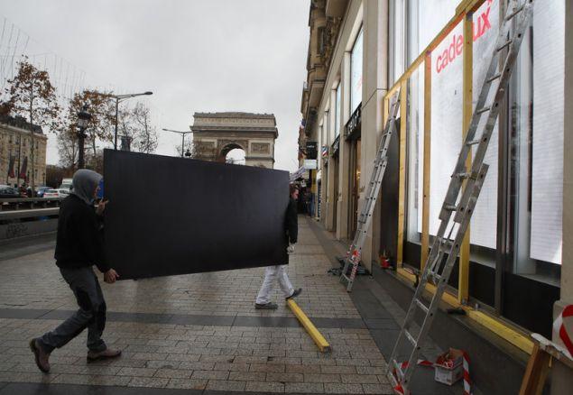 Εργάτες καλύπτουν τις βιτρίνες καταστημάτων στη λεωφόρο Champs Elysees (Φωτογραφία: ΑΡ)