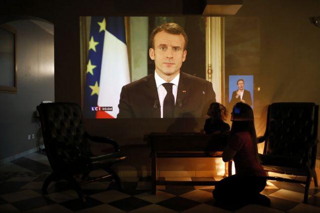Μητέρα με το παιδί της στη Λυόν, παρακολουθούν τις εξαγγελίες Μακρόν -Φωτογραφία: AP Photo/Laurent Cipriani