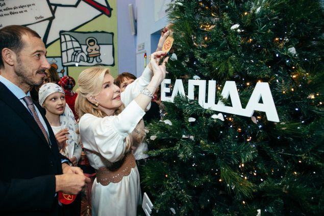 """Η Μαριάννα Β. Βαρδινογιάννη τοποθετεί το στολίδι με τις ευχές της στο """"Δέντρο των Ευχών"""""""