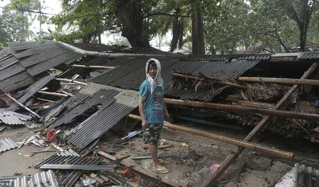 Eπιζώντες επιθεωρούν τις ζημιές που προκάλεσε το τσουνάμι στην Καριτα της Ινδονησίας (Φωτογραφία: ΑΡ)