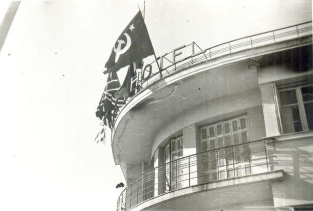 Στον τελευταίο όροφο του ξενοδοχείου Ακροπόλ ήταν τοποθετημένες στα κάγκελα τέσσερις σημαίες, μια Ρωσική (σφυροδρέπανο), μια Αγγλική μια Ελληνική και μια Αμερικανική που μόλις διακρίνεται.