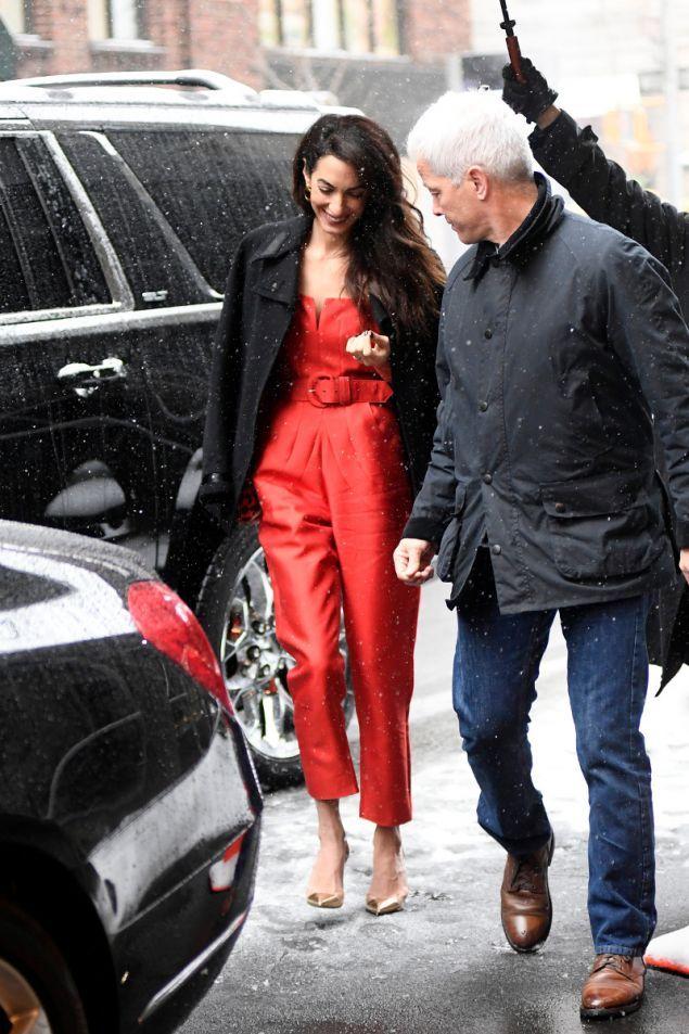 Η Αμάλ Κλούνεϊ με κατακόκκινη ολόσωμη φόρμα και χρυσά πέδιλα. Η Αμάλ μαζί με την Σερένα Γουίλιαμς λέγεται ότι διοργάνωσαν το baby shower