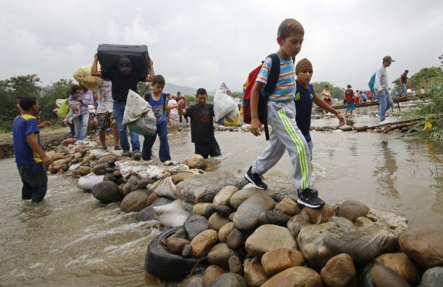 Απηυδισμένοι Βενεζουελάνοι περνούν με τα παιδιά τους από αυτοσχέδια γέφυρα στην Κολομβία (Φωτογραφία: ΑΡ)