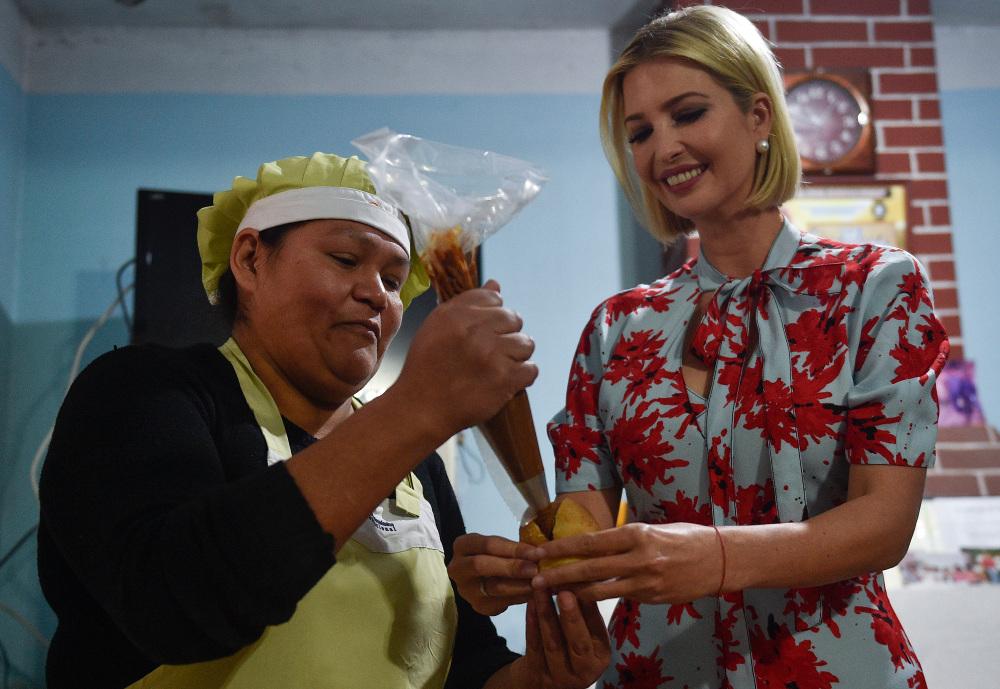 Με προσποιητό χαμόγελο και κρατώντας το γλυκό σαν να είναι κάτι αηδιαστικό, η Ιβάνκα Τραμπ βοηθά την ιδιοκτήτρια του αρτοποιείου να γεμίσει με κρέμα την σφολιάτα