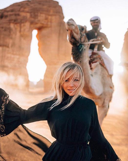 Influencer ποζάρει στην έρημο της Σαουδικής Αραβίας με έναν καμηλιέρη πίσω